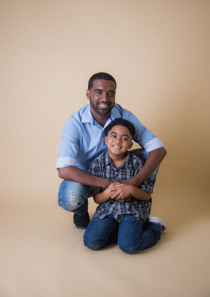 Oahu Family Photographer, father and son kneeling down and posing in studio with tan background