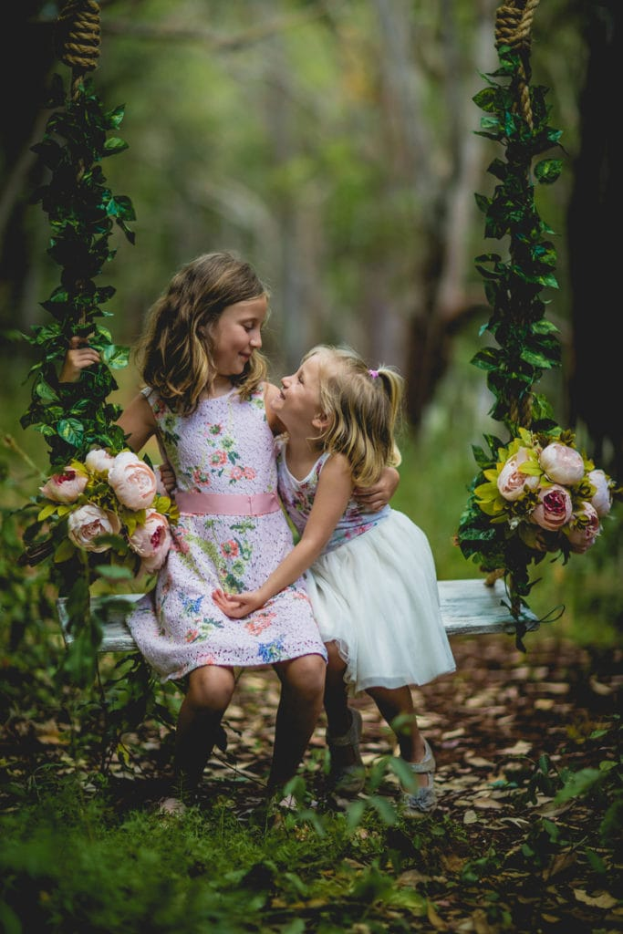Oahu Family Photographer, two young sisters sitting on a bench swing together