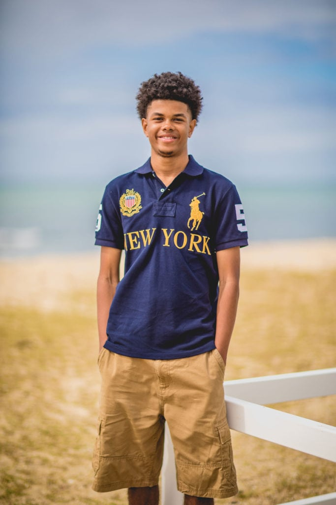 Oahu Family Photographer, high school senior boy leaning against a white rail
