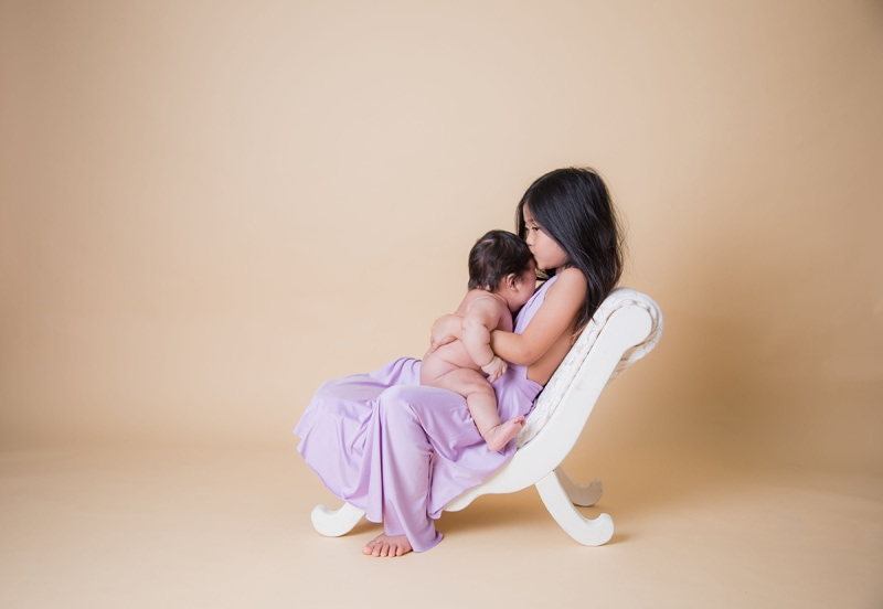 Oahu Family Photographer, young sister holding newborn baby on her lap